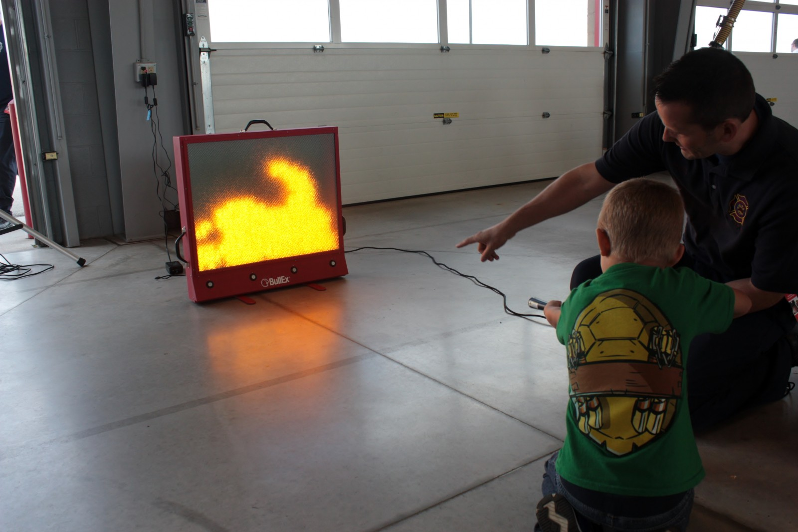 GCFD Firefighter Instructing Child on Fire Extinguisher Use